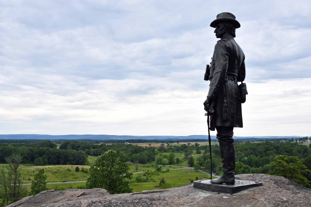 Statue of General Gouverneur Warren on Little Round Top facing Plum Run. The Devil's Den is to the left (not shown). Cemetery Ridge extends to the right.